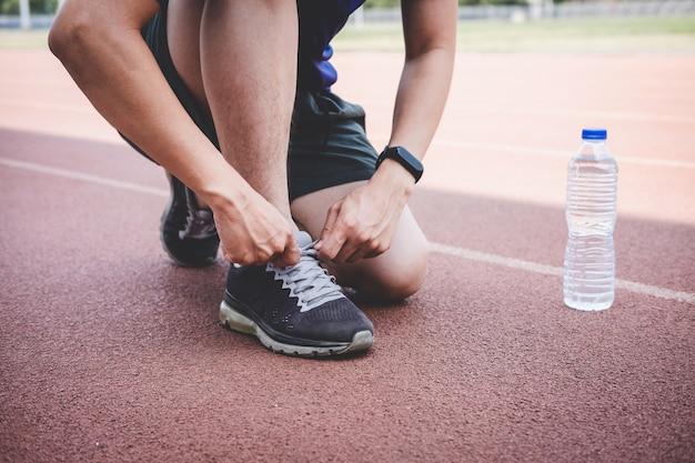 Homem jovem atleta correndo na pista de estrada, exercício treino bem-estar e corredor amarrar cadarços