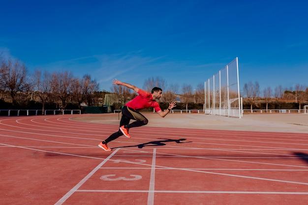 Homem jovem atleta correndo nas pistas. luz do dia. conceito de esportes