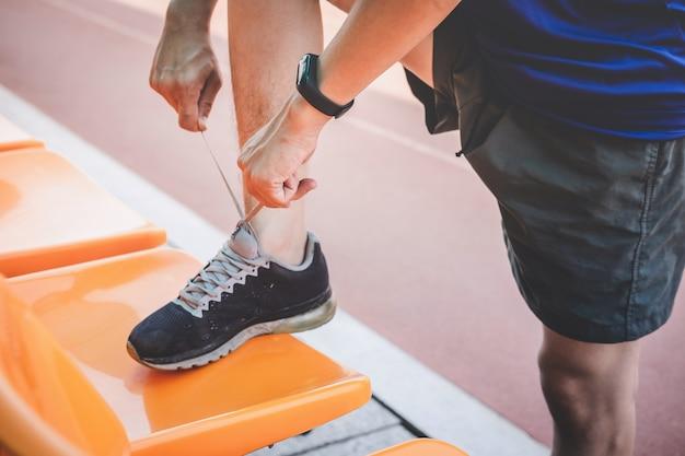 Homem jovem atleta fitness correndo na pista de estrada, bem-estar de treino exercício e corredor amarrar cadarços