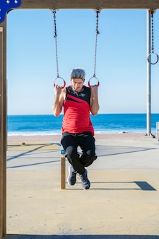 Homem jovem atleta pendurado nos anéis, fazendo o exercício de pull-up
