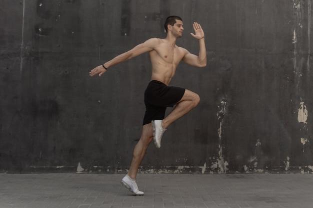Homem jovem atleta, torso nu, correndo contra uma parede cinza