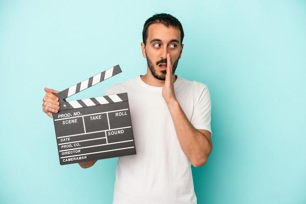 Homem jovem ator caucasiano segurando claquete isolada em fundo azul está contando uma notícia secreta de travagem e olhando para o lado