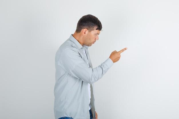 Homem jovem avisando alguém com gesto do dedo em uma camiseta cinza e parecendo nervoso