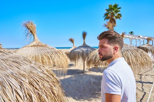 Homem jovem barba em uma praia com guarda-sol