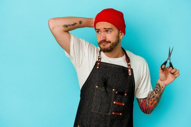 Homem jovem barbeiro tatuado isolado em um fundo azul, tocando a parte de trás da cabeça, pensando e fazendo uma escolha.