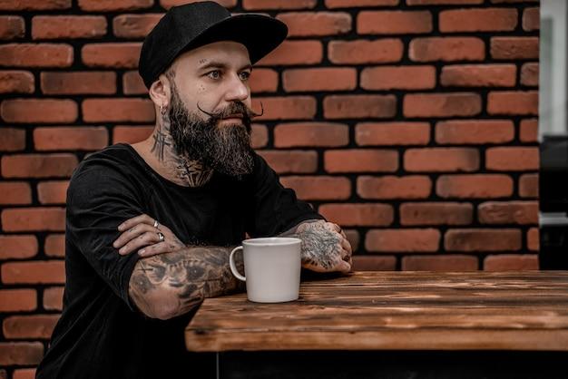 Homem jovem barbudo bebendo café. homem moderno, tendo a pausa para o café. conceito de estilo de vida das pessoas.