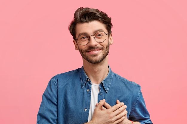 Homem jovem barbudo de coração amável e satisfeito mantém ambas as palmas das mãos no peito, tem uma aparência positiva e expressa sentimentos verdadeiros