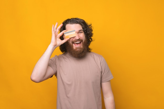 Homem jovem barbudo hippie com cabelo comprido encaracolado mostrando cartão de crédito