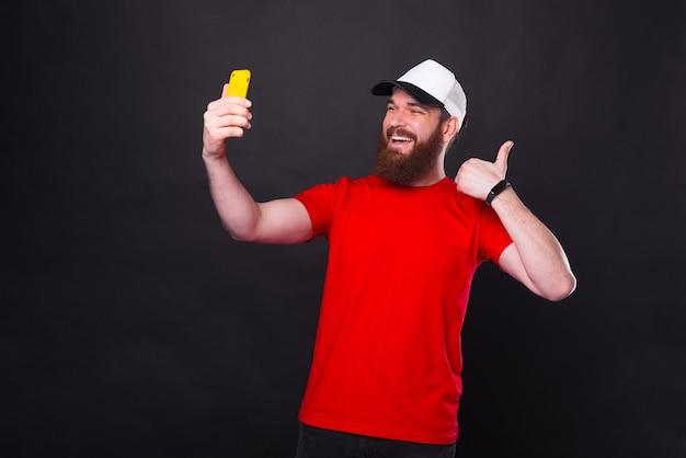 Homem jovem barbudo hippie espantado com uma t-shirt vermelha a tirar uma selfie
