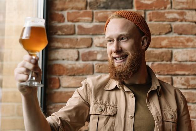 Homem jovem barbudo hipster segurando copo com cerveja, verificando a qualidade do álcool, testando cerveja em cervejaria