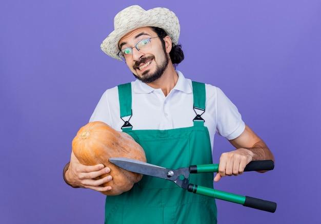 Homem jovem barbudo jardineiro vestindo macacão e chapéu segurando abóbora olhando para ela sorrindo e cortador de cerca viva olhando para frente sorrindo com uma cara feliz em pé sobre a parede azul
