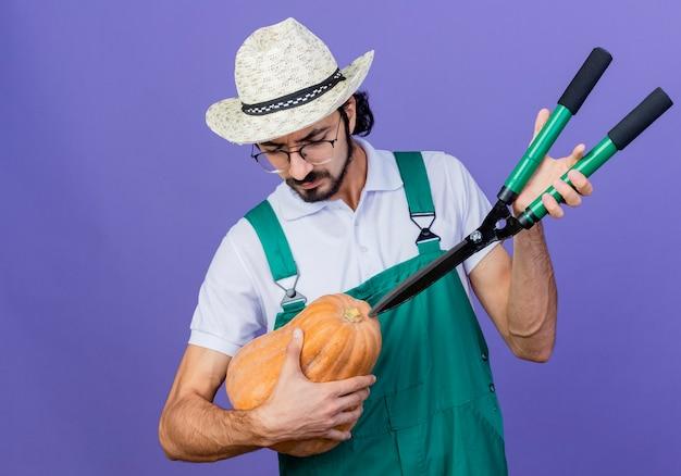 Homem jovem barbudo jardineiro vestindo macacão e chapéu segurando uma abóbora e um cortador de cerca viva olhando para uma abóbora com uma cara séria