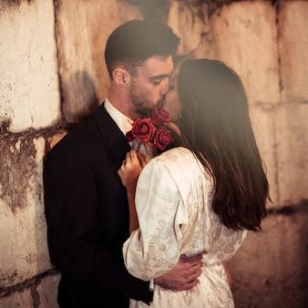Homem jovem, beijando, mulher, inclinar-se, parede