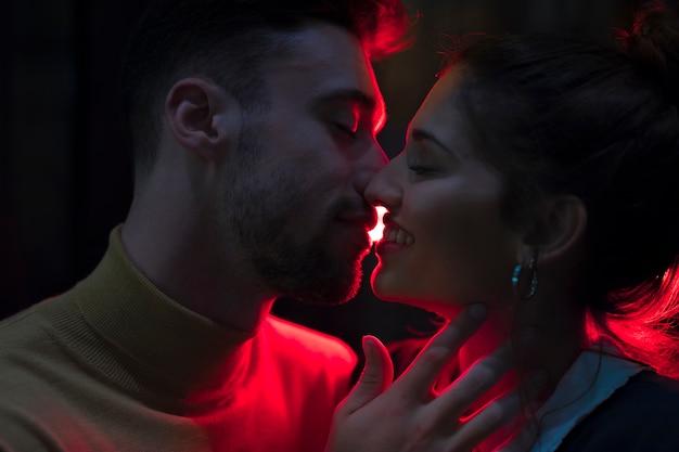 Homem jovem, beijando, mulher sorridente, iluminado, por, luzes vermelhas