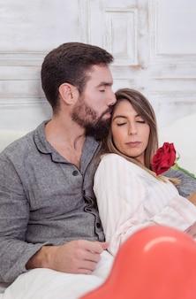 Homem jovem, beijando, mulher, testa, cama