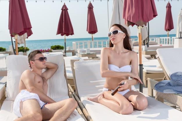 Homem jovem bonito admirando sua namorada enquanto está sentado na espreguiçadeira e aplicando a loção de protetor solar no corpo em um clima ensolarado no resort.