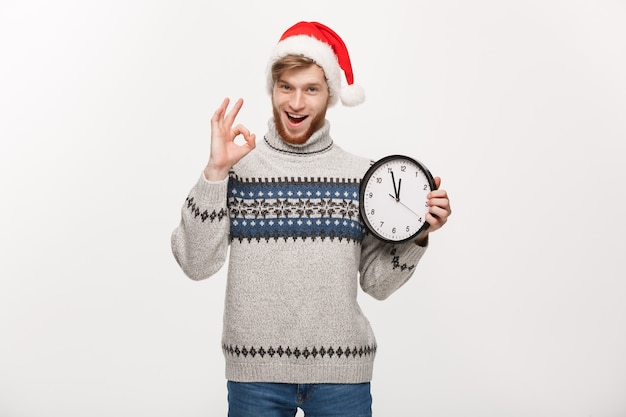 Homem jovem bonito barba de suéter com relógio branco, dando sinal de ok.