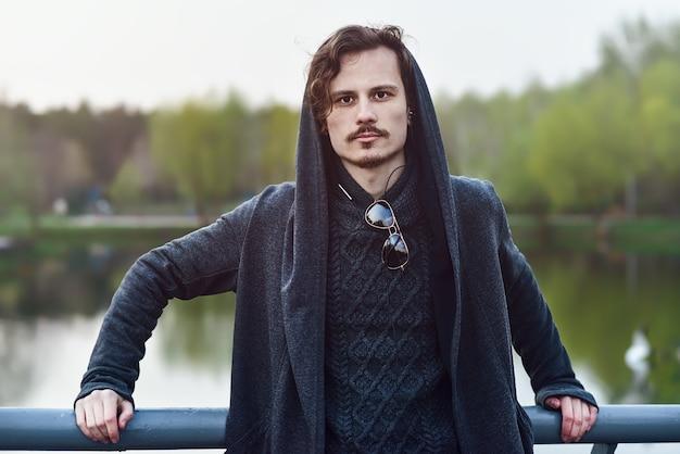 Homem jovem bonito cabelo encaracolado no manto em pé na ponte.