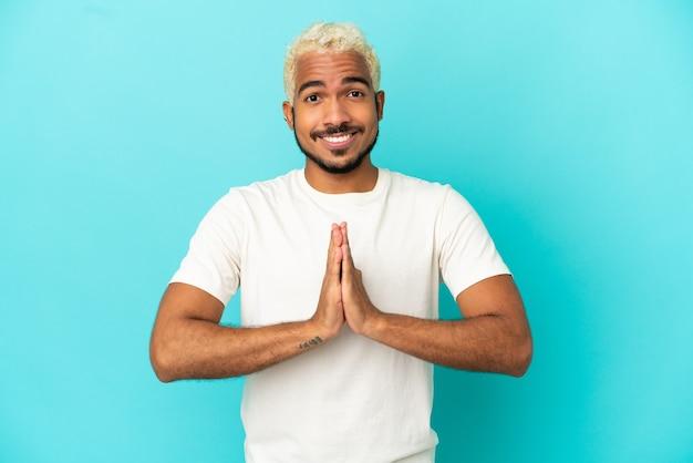 Homem jovem bonito colombiano isolado em um fundo azul mantém as palmas das mãos juntas. pessoa pede algo