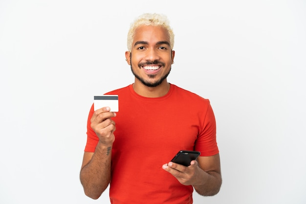 Homem jovem bonito colombiano isolado no fundo branco, comprando com o celular com cartão de crédito