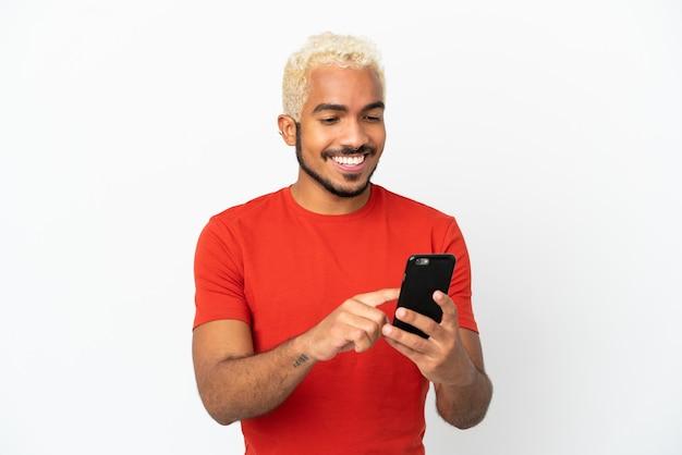 Homem jovem bonito colombiano isolado no fundo branco enviando uma mensagem ou e-mail com o celular