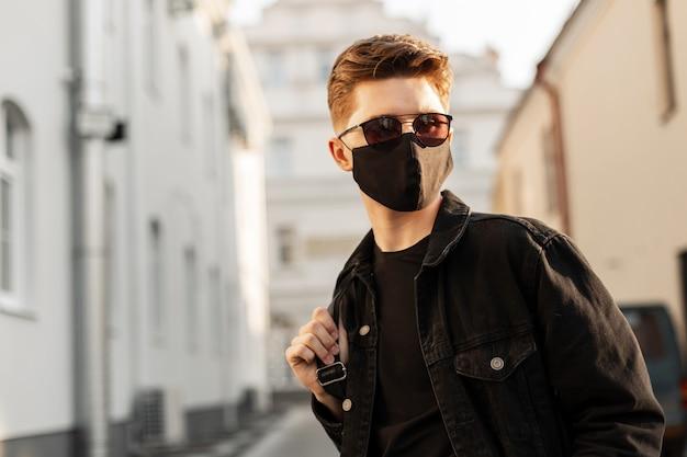 Homem jovem bonito da moda em óculos de sol com mochila na máscara facial de poluição