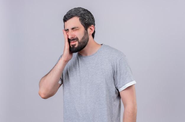 Homem jovem bonito e dolorido, fechando os olhos e colocando a mão na bochecha, sofrendo de dor de dente isolada no branco com espaço de cópia