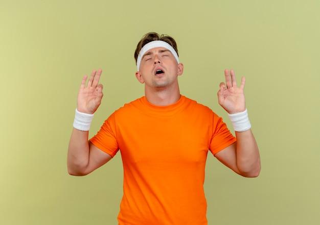 Homem jovem bonito e tranquilo, desportivo, usando bandana e pulseiras, fazendo sinais de ok com os olhos fechados, isolado no fundo verde oliva