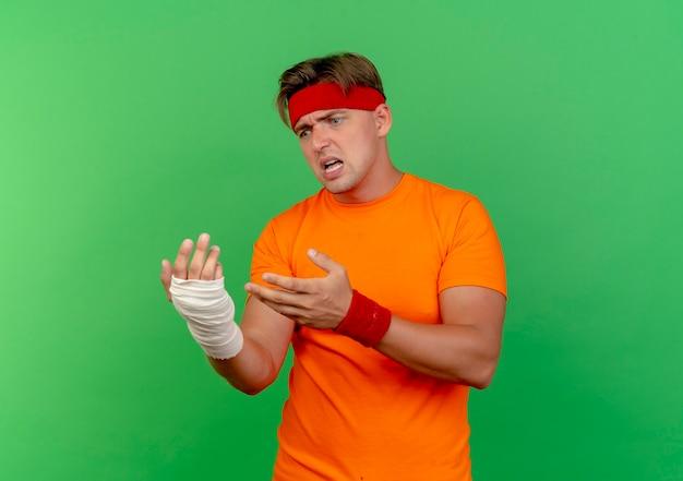 Homem jovem bonito e zangado, esportivo, usando bandana e pulseiras, olhando e apontando para o pulso ferido, envolto em bandagem isolada em verde com espaço de cópia