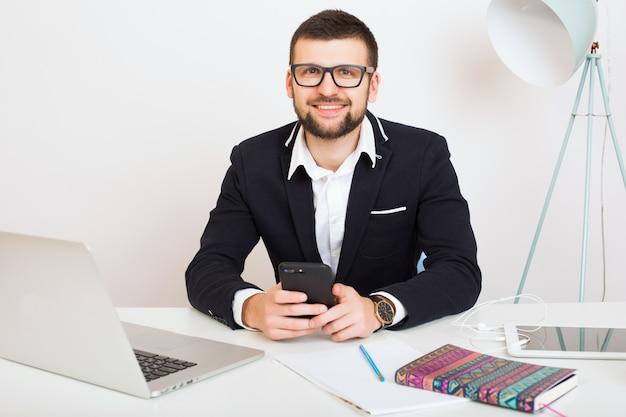 Homem jovem bonito elegante hipster em jaqueta preta sentado à mesa do escritório, estilo empresarial, camisa branca, isolado, trabalhando, laptop, inicializar, local de trabalho, falando no smartphone, sorrindo, positivo