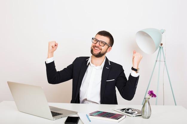 Homem jovem bonito elegante hipster em jaqueta preta sentado à mesa do escritório, estilo empresarial, camisa branca, isolado, trabalhando no laptop, arranque, local de trabalho, vitória