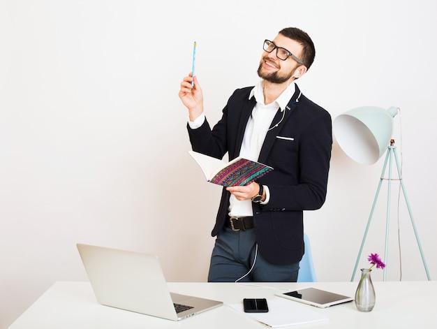 Homem jovem bonito elegante hipster em jaqueta preta trabalhando na mesa do escritório, estilo empresarial, camisa branca, isolado, laptop, inicializar, local de trabalho, pensamento, documentos