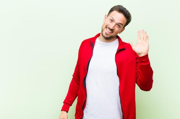 Homem jovem bonito esportes ou monitor sorrindo feliz e alegremente, acenando com a mão, dando as boas-vindas e cumprimentando-o ou dizendo adeus contra o apartamento