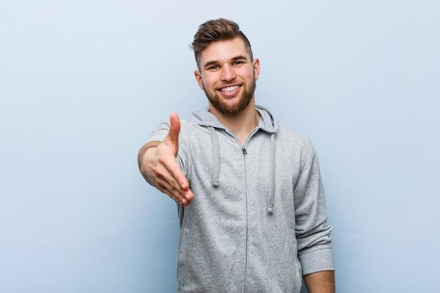 Homem jovem bonito fitness esticando a mão no gesto de saudação.