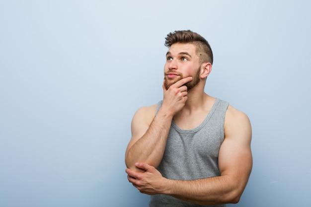 Homem jovem bonito fitness olhando de soslaio com expressão duvidosa e cética