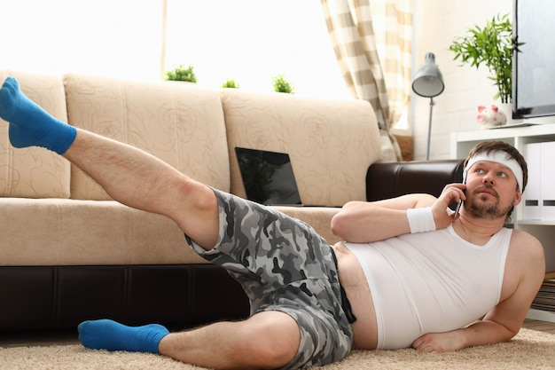 Homem jovem bonito fitness situa-se no tapete gordo com
