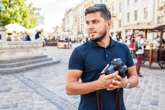 Homem jovem bonito hippie andando com uma câmera fotográfica na rua da cidade velha