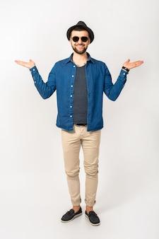 Homem jovem bonito hippie, roupa de estilo moderno, camisa jeans, calças, óculos de sol, chapéu, feliz, sorridente, emoção positiva, isolado, mãos vazias para cima, compare