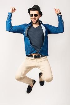 Homem jovem bonito hippie, roupa de estilo moderno, camisa jeans, calças, óculos de sol, chapéu, feliz, sorridente, emoção positiva, isolado, pulando, alegre