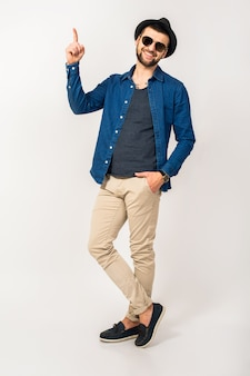 Homem jovem bonito hippie, roupa de estilo moderno, camisa jeans, calças, óculos de sol, chapéu, isolado, pulando, alegre, dedo apontando