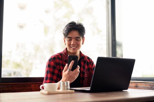 Homem jovem bonito hipster asiático feliz usando telefone e laptop na cafeteria