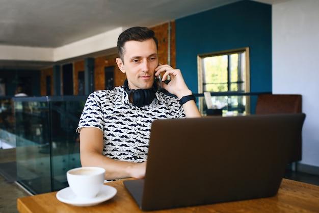 Homem jovem bonito hipster está usando laptop, falando do telefone móvel na cantina.