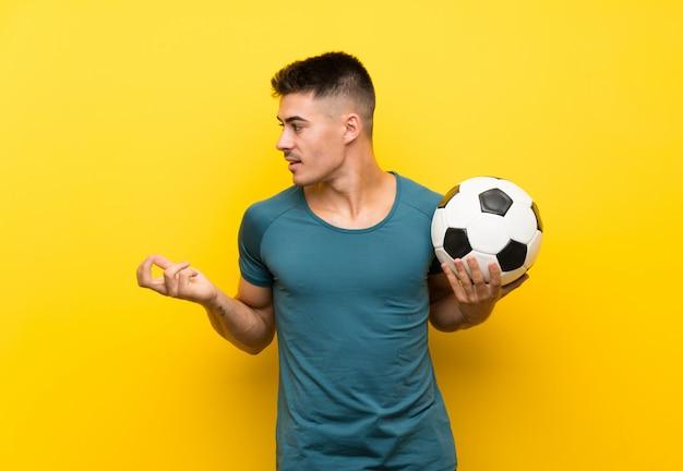 Homem jovem bonito jogador de futebol com expressão facial de surpresa