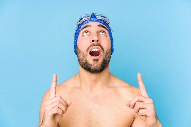 Homem jovem bonito nadador isolado apontando para cima com a boca aberta.