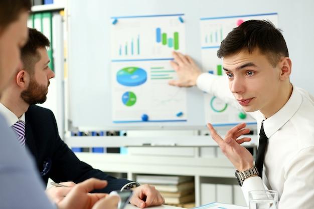 Homem jovem bonito professor de terno com placa de seminário de grupo de trabalho com plano de treinamento gráfico. palestrante para candidatos em reciclagem de gestão de estatísticas financeiras, etiqueta empresarial, espírito corporativo