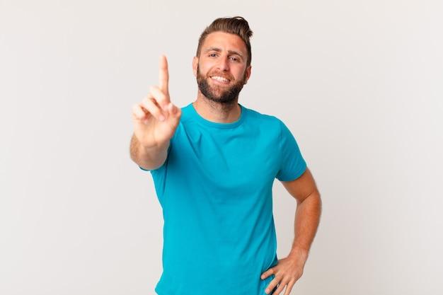 Homem jovem bonito sorrindo com orgulho e com confiança, fazendo o número um. conceito de fitness