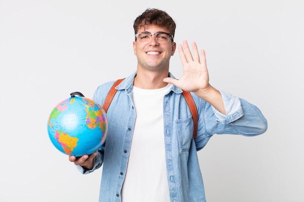 Homem jovem bonito sorrindo e parecendo amigável, mostrando o número cinco. estudante segurando um mapa do globo