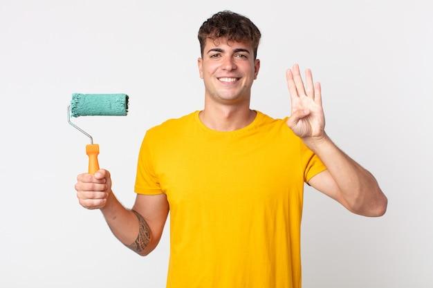 Homem jovem bonito sorrindo e parecendo amigável, mostrando o número quatro. conceito de pintura de casa