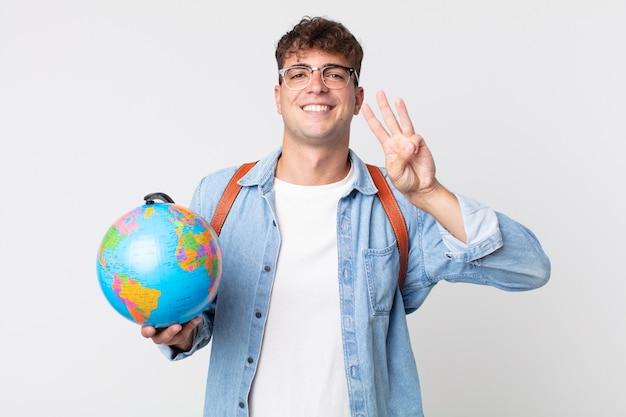 Homem jovem bonito sorrindo e parecendo amigável, mostrando o número três. estudante segurando um mapa do globo