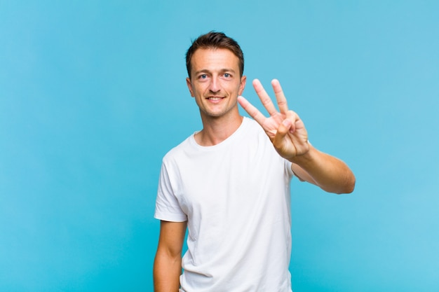 Homem jovem bonito sorrindo e parecendo amigável, mostrando o número três ou terceiro com a mão para a frente, em contagem regressiva